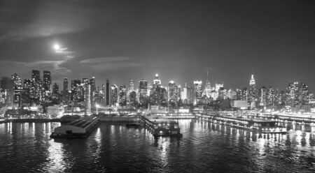 hudson river: The panorama of Midtown Manhattan coast with piers viewed from the Hudson River at night in New York City, USA.