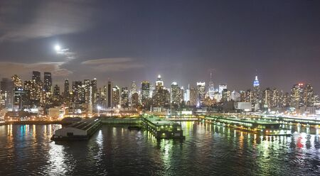 midtown manhattan: The panorama of Midtown Manhattan coast with piers viewed from the Hudson River at night in New York City, USA.
