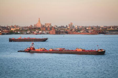 tugging: Tugboats sailing in the Upper Bay with a view of the Brooklyn coast in the background in New York City, USA. Stock Photo