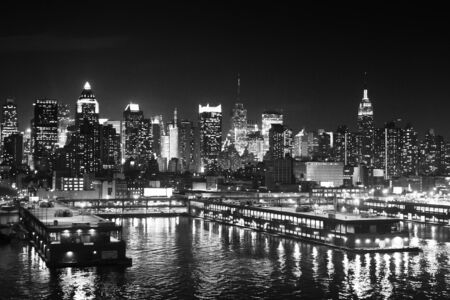 hudson river: The panorama of Midtown Manhattan coast with ships pier viewed from the Hudson River at night in New York City, USA.