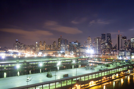 midtown manhattan: A view of a parking lot on top of a pier building and the panorama of Midtown Manhattan at night in New York City, USA. Stock Photo