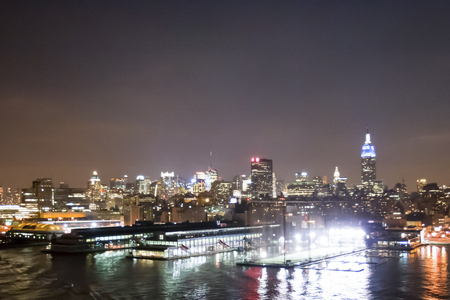 midtown manhattan: NEW YORK CITY, USA - MARCH 25: The panorama of Midtown Manhattan coast with  Chelsea Piers Sports and Entertainment Complex seen from Hudson River at night on March 25th, 2005 in New York City, USA. Editorial