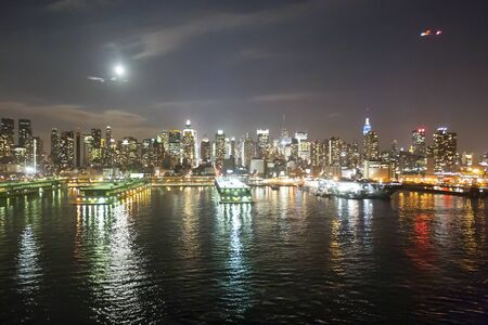 intrepid: NEW YORK CITY, USA - MARCH 25 : The panorama of Midtown Manhattan coast with the Intrepid Sea, Air and Space Museum viewed from the Hudson River at night on March 25th, 2005 in New York City, USA.