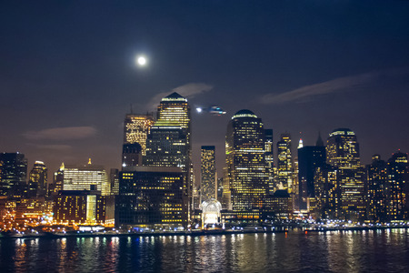 The Manhattan Financial District viewed from the New York Harbor at night with a helicopter flying in the air in New York City, USA.