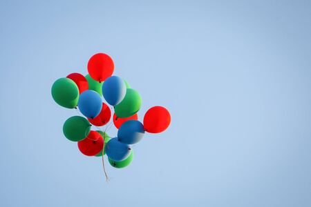 flying float: A view from below of a group of colorful balloons flying in the air. Stock Photo