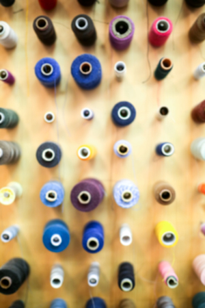 displayed: Blurry background of a large group of displayed bobbins of thread.