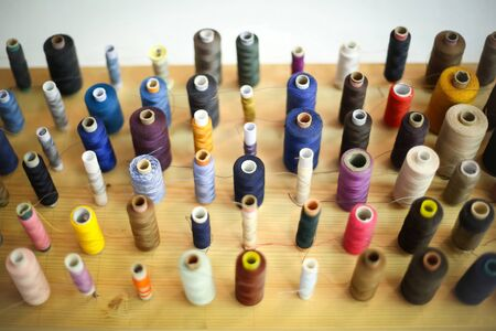 displayed: A high angle view of a large group of displayed bobbins of thread on a wooden board.
