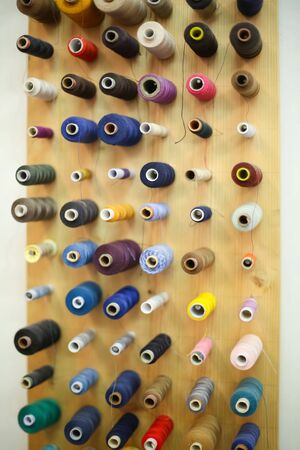 displayed: A directly above view of a large group of displayed bobbins of thread on a wooden board. Stock Photo