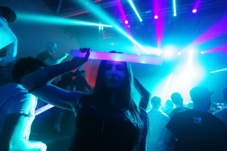 sensation: ZAGREB, CROATIA - APRIL 9, 2016 : A woman from the audience with an illuminating stick posing on La Fiesta Stage by Sensation party in Hypo center in Zagreb, Croatia.