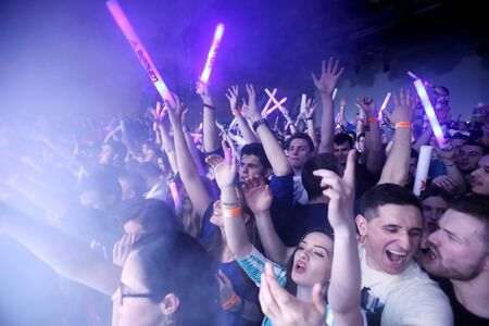fiesta popular: ZAGREB, CROATIA - APRIL 9, 2016 : The audience with illuminating sticks on La Fiesta Stage by Sensation party in Hypo center in Zagreb, Croatia.