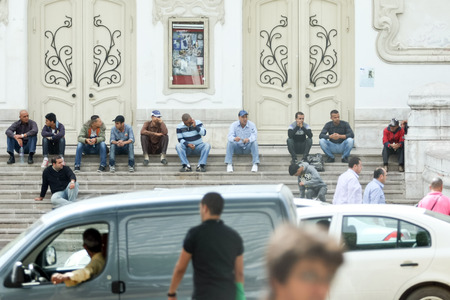 socializando: TUNIS, TUNISIA - SEPTEMBER 14, 2012 : Muslim men sitting and socializing on the steps of a building in the Avenue Habib Bourguiba in Tunis,Tunisia.