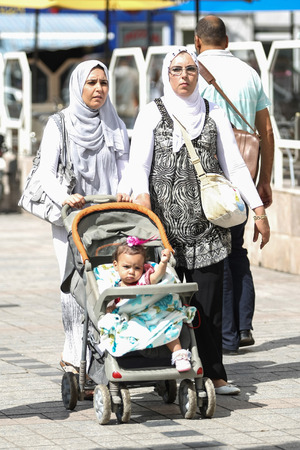 toddler walking: TUNIS, TUNISIA - SEPTEMBER 14, 2012 : Muslim women with a toddler walking in the city streets in Tunis,Tunisia.