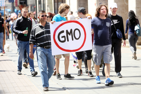 protesters: ZAGREB, CROATIA - MAY 21, 2016 :  Protesters march with signs raised through Zagreb in a protest against US biotechnology group Monsanto and against TTIP agreement.