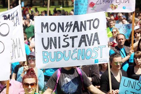 modifying: ZAGREB, CROATIA - MAY 21, 2016 :  Protesters march with signs raised through Zagreb in a protest against US biotechnology group Monsanto and against TTIP agreement. A sign that says Monsanto destroys the future. Editorial