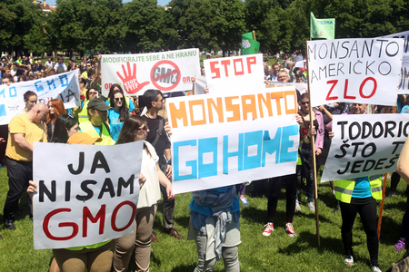 modifying: ZAGREB, CROATIA - MAY 21, 2016 :  Protesters march with signs raised through Zagreb in a protest against US biotechnology group Monsanto and against TTIP agreement.