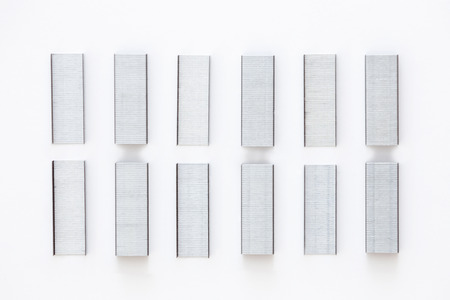 lined up: A top view of a group of staples lined up on white background. Stock Photo