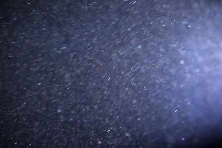 dispersed: An abstract view of illuminated dust particles spread out.