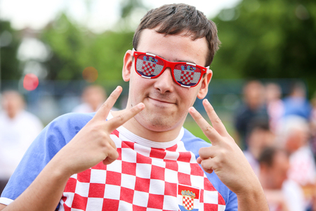 prop: ZAGREB,CROATIA-JUNE 17,2016 : Croatian football fans on the playground at Jarun, watching EURO 2016 match Czech Republic vs Croatia in Zagreb,Croatia.Boy with the glasses as a prop and with a two fingers up sign for a victory.