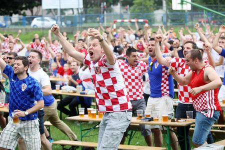 scored: ZAGREB,CROATIA - JUNE 17,2016 : Croatian football fans on the playground at Jarun, watching EURO 2016 match Czech Republic vs Croatia in Zagreb,Croatia.Fans celebrate a goal that is scored by Croatia.