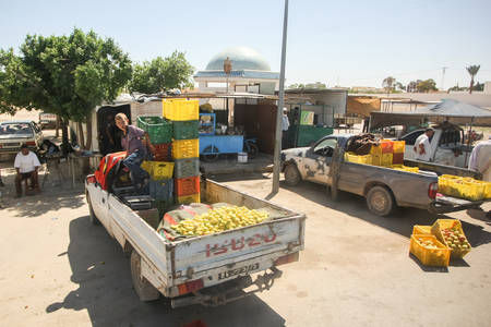 bir: BIR AL HUFFAY, TUNISIA -  SEPTEMBER 16, 2012 : People packing groceries on pick up trucks at food market in Bir Al Huffay, Tunisia.