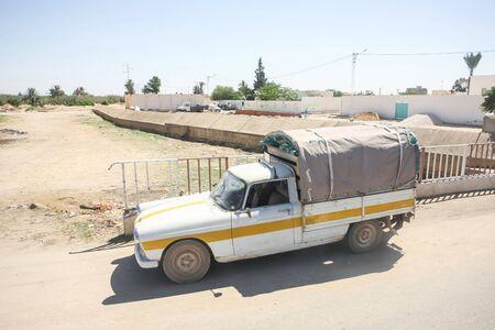 bir: BIR AL HUFFAY, TUNISIA -  SEPTEMBER 16, 2012 : A pick up truck parked on the main road in Bir Al Huffay, Tunisia.