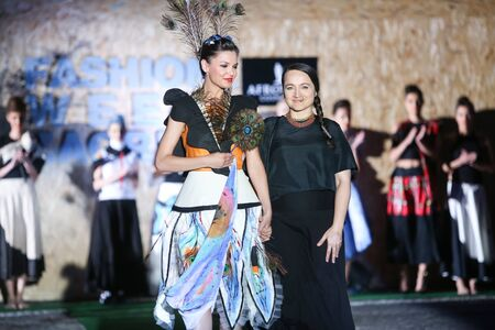 green and gold: ZAGREB, CROATIA - JUNE 3, 2016 : Fashion designer Mandali Mendrilla with model wearing clothes designed by her on the Fashion Week Zagreb fashion show in the park Green Gold Centre in Zagreb, Croatia.
