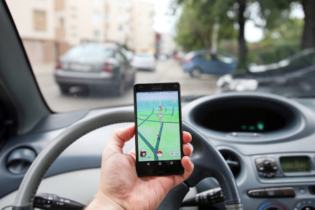 VELIKA GORICA, CROATIA- JULY 15, 2016 : A gamer using a smartphone to play Pokemon Go while driving a car. Pokemon Go is a free-to-play augmented reality mobile game developed by Nintendo. Stock Photo - 59471729
