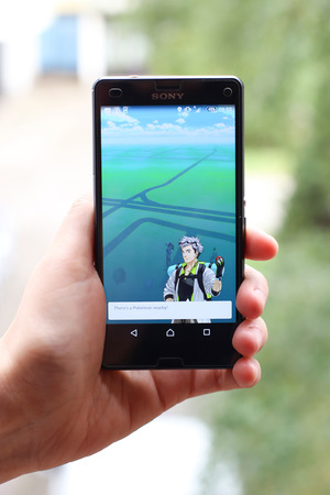 nintendo: VELIKA GORICA, CROATIA- JULY 15, 2016 : A gamer using a smartphone to play Pokemon Go in Velika Gorica, Croatia. Pokemon Go is a free-to-play augmented reality mobile game developed by Nintendo.