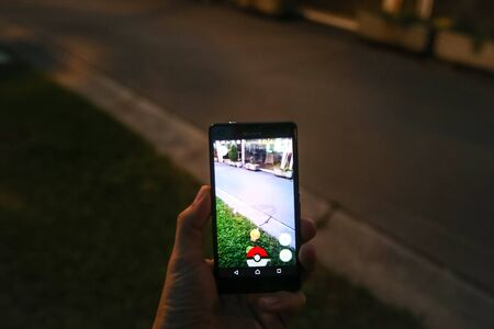 finds: VELIKA GORICA, CROATIA- JULY 15, 2016 : Gamer finds a pokemon on the street using a smartphone to play Pokemon Go. Pokemon Go is a free-to-play augmented reality mobile game developed by Nintendo.