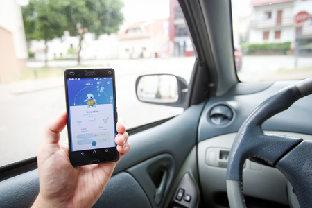nintendo: VELIKA GORICA, CROATIA- JULY 15, 2016 : A gamer using a smartphone to play Pokemon Go while driving a car. Pokemon Go is a free-to-play augmented reality mobile game developed by Nintendo. Editorial