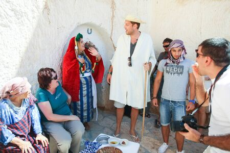 matmata: MATMATA,TUNISIA - SEPTEMBER 17, 2012 : Couple dressed in a berbers clothing with a group of tourists in front of a troglodyte home tasting local food specialties in berber village in Matmata,Tunisia. Editorial