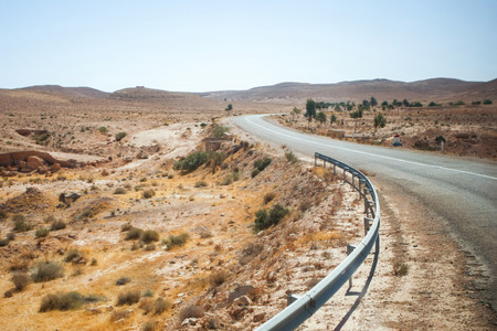 troglodyte: A road passing through the rocky desert of Matmata in south Tunisia. Matmata is famous for its troglodyte cave dwellings. Stock Photo