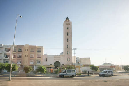 residential neighborhood: TUNISIA - A view of residential neighborhood with cars in the street and a mosque with tower in Tunisia.
