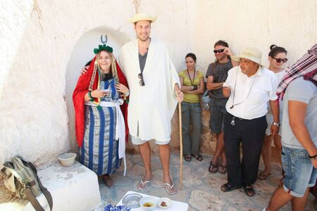 troglodyte: MATMATA, TUNISIA - SEPTEMBER 17, 2012 : Couple dressed in a berbers clothing with a group of tourists in front of a troglodyte home tasting local food specialties in berber village in Matmata, Tunisia.