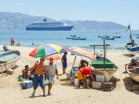 fish selling: ACAPULCO, MEXICO - MARCH 11, 2006 : People selling fresh fish on the beach with Queen Mary 2 cruise ship in the background in Acapulco, Mexico.