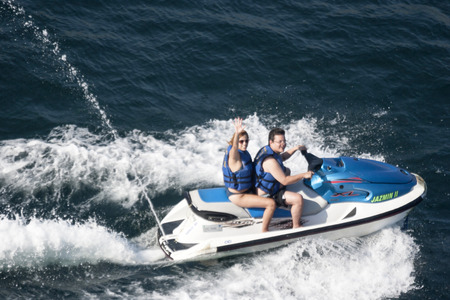 ACAPULCO, MEXICO - FEBRUARY 19, 2006 : Two people riding jet ski and waving to the camera in the bay of Acapulco, Mexico. 新聞圖片