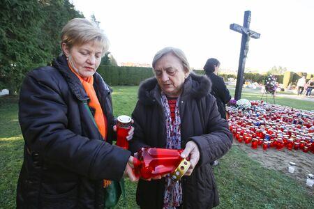 all saints day: VELIKA GORICA, CROATIA - NOVEMBER 1, 2016 : Two women lighting lampions at cemetery on All Saints day in Velika Gorica, Croatia.