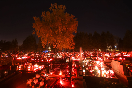 VELIKA GORICA, CROATIA - NOVEMBER 1, 2016 : A night view of ornated graves with flowers and burning lampions at cemetery on All Saints day in Velika Gorica, Croatia. Editorial