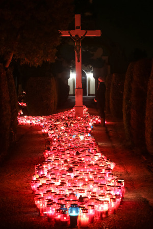 burning bush: A night view of a woman praying in front of the cross with a large group of burning lampions on the floor at cemetery in Velika Gorica, Croatia. Stock Photo