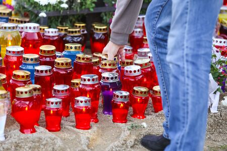 A man placing a lampion on the floor among other burning lampions on All Saints day on cemetery in Croatia. Stock Photo