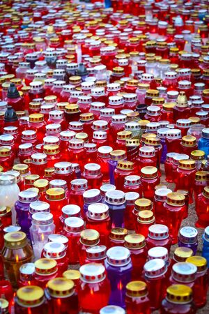 all souls' day: A large group of candles lit for the deceased family members and friends lined up on the floor at cemetery on All Saints day. Stock Photo