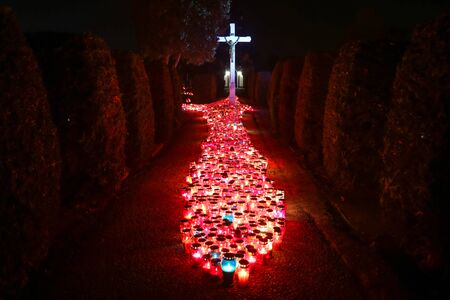 hundreds: A night view of hundreds of candles lit for the deceased family members and friends in front of the cross at city cemetery on All Saints day in Velika Gorica, Croatia. Stock Photo