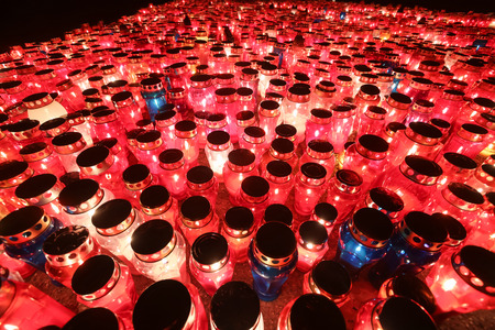 A night view of hundreds of candles lit for the deceased family members and friends lined up on the floor at cemetery on All Saints day. Stock Photo