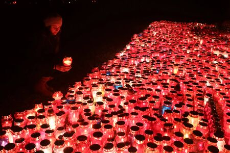 A night view of a woman holding a lampion in front of a large group of burning lampions on the floor at cemetery in Croatia.