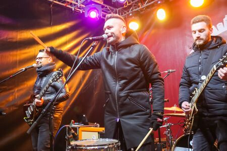 ZAGREB, CROATIA - DECEMBER 1th, 2016: Advent time in city center of Zagreb, Croatia. Famous croatian rock band Vatra performing on stage in front of Art gallery Klovicevi Dvori in the upper old town. Editorial