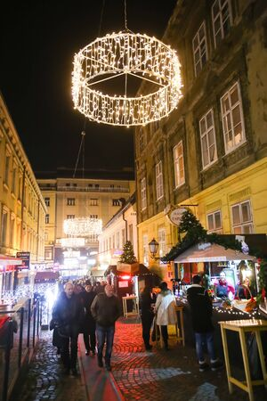 advent time: ZAGREB, CROATIA - DECEMBER 1th, 2016: Advent time in city center of Zagreb, Croatia. People sightseeing ornated streets with souvenir and food stands.