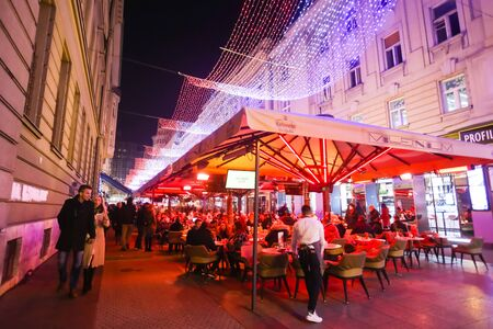 advent time: ZAGREB, CROATIA - DECEMBER 1th, 2016: Advent time in city center of Zagreb, Croatia. People sitting in coffee shops in ornated Bogoviceva street.
