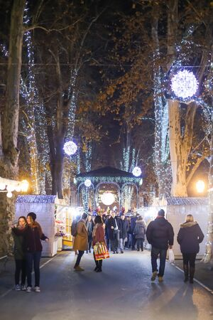 advent time: ZAGREB, CROATIA - DECEMBER 1th, 2016: Advent time in city center of Zagreb, Croatia. People gathering in the Zrinjevac park ornate with food stands and illuminating trees. Editorial