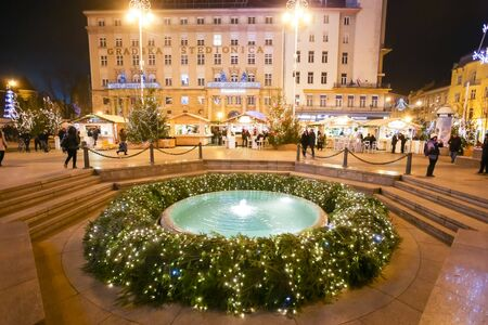 advent time: ZAGREB, CROATIA - DECEMBER 1th, 2016: Advent time in city center of Zagreb, Croatia. Advent wreath around the water fountain Mandusevac on central Jelacic Square.