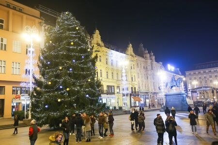 advent time: ZAGREB, CROATIA - DECEMBER 1th, 2016: Advent time in city center of Zagreb, Croatia. People on central Jelacic square with a large ornated pine tree. Editorial